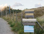Wooden Empty Blank Way Pointers And Sign Boards To Put Your Text In With Green Grass A Fence And A R poster