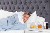 Ill Boy Suffering From Cold In Bed And Cough Remedies On Bedside Table poster