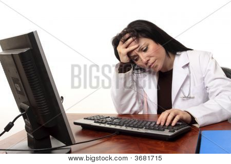 Overworked Tired Doctor At Computer