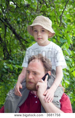 Father With Son On Shoulders Talks  By A Mobile Phone