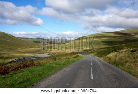 Countryside Road Alongside The River Elan In Wales, Uk.
