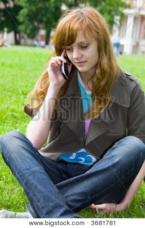 The Girl Talks By A Mobile Phone In Park.