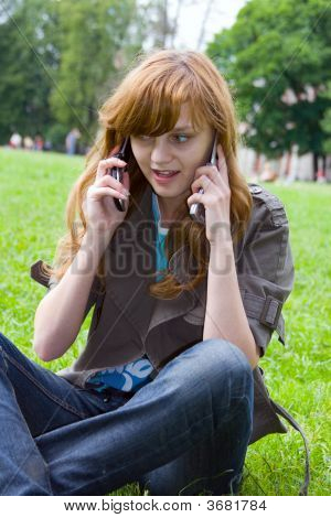 The Girl Talks By Two Mobile Phones, Sitting On A Grass
