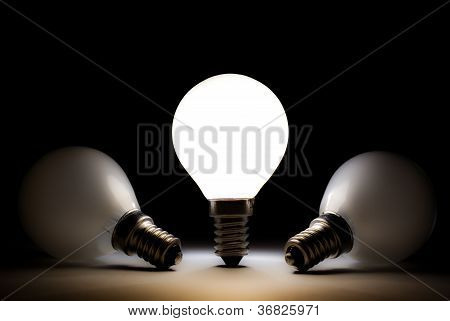 One light bulb shining in a dark space with other dead bulbs