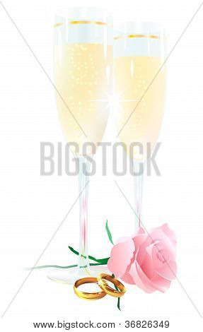 Two glasses of champagne, roses and rings