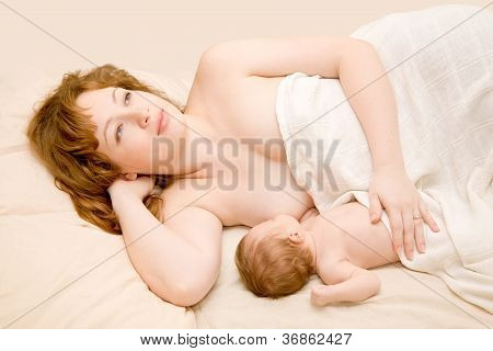 mother is breast feeding a newborn baby