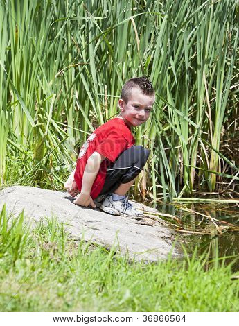 Young Boy Near Pond At The Park