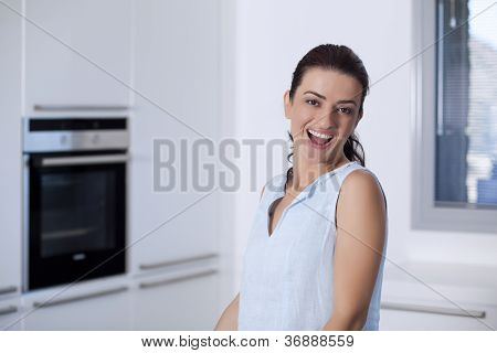 Portrait Of A Beautiful Smiling Woman In The Kitchen