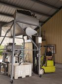 pic of crusher  - Worker dumping red wine grapes into a destemmer and crusher machine - JPG