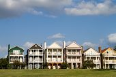 picture of memphis tennessee  - Upscale townhomes for the wealthy built on a grass hill in a row against a cloudy blue sky in Memphis Tennessee - JPG