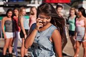 image of coy  - Shy teenage Filipino girl looking down with friends nearby - JPG