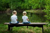 stock photo of fish pond  - Little girls are fishing on lake in forest - JPG