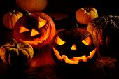 stock photo of scary face  - closeup of scary halloween pumpkins on dark background - JPG