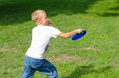 stock photo of frisbee  - Little boy playing frisbee on green grass - JPG
