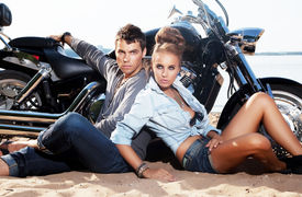 stock photo of carnal  - Extreme couple sitting by motorcycle on the beach - JPG