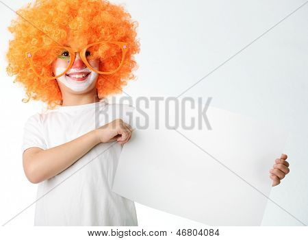 Portrait of happy funny clown kid holding copy space banner for your message