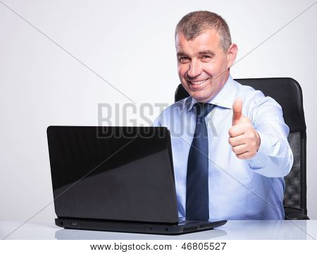senior bussines man sitting at his laptop and showing the thumbs up sign while smiling to the camera. on gray background