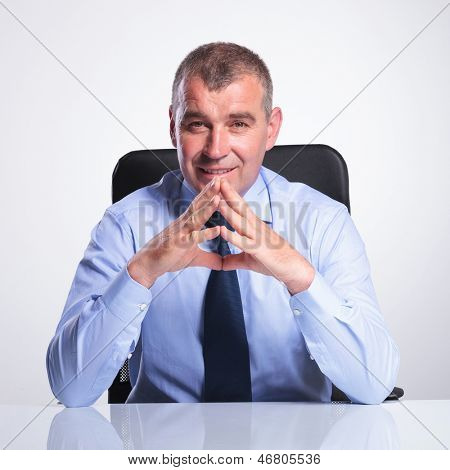 senior bussines man sitting at his office with his hands together, elbows on the table and smiling to the camera. on gray background