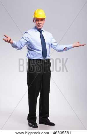 full length picture of a senior engineer welcoming you with his arms opened.on gray background