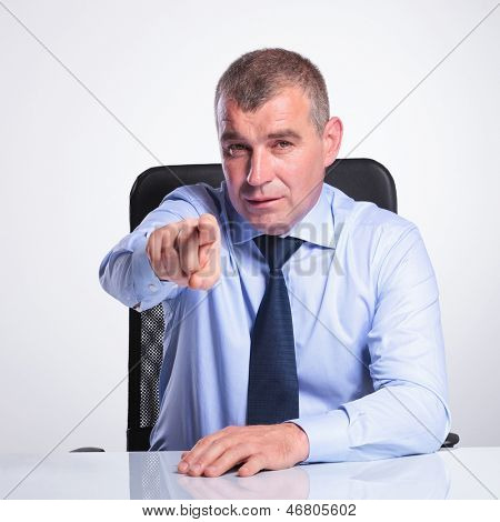 senior bussines man sitting at bureau and pointing and looking at the camera. on gray background