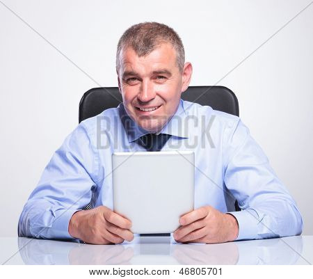 senior business man sitting at his desk and holding a tablet while smiling to the camera . on gray background
