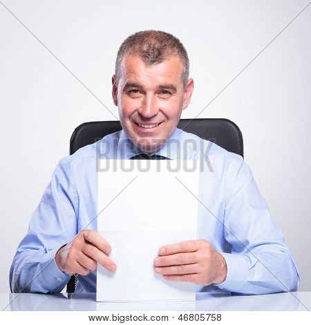 portrait of a senior business man sitting at his desk and holding some documents with a smile on his face. on gray background