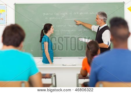 senior teacher pointing at chalkboard with student standing in front of the class