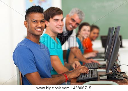 group of students and teacher in computer class looking at the camera