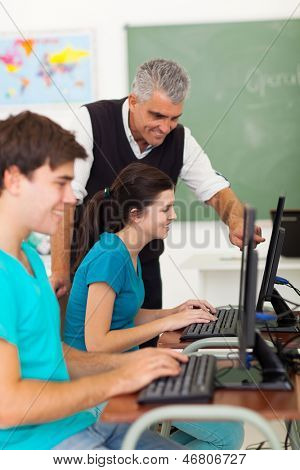 cheerful middle aged teacher helping high school students with computer work