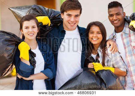 cheerful young volunteers with garbage bag after cleaning the streets