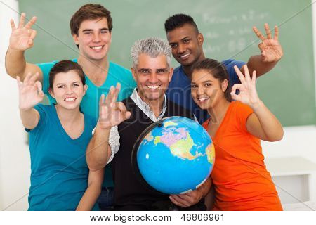 cheerful high school geography students and teacher giving ok hand sign in classroom