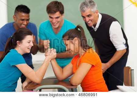 cheerful female high school students playing arm wrestling in classroom