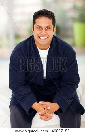 handsome indian man in pajamas sitting on bed
