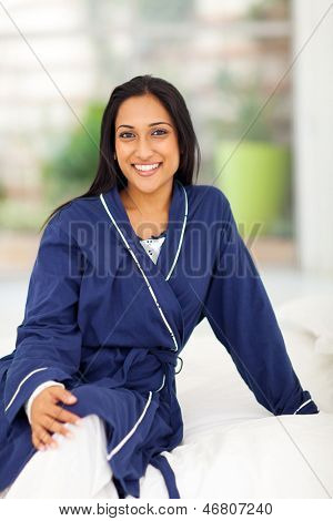 portrait of young indian woman in pajamas sitting on bed