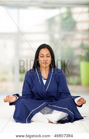 beautiful indian woman meditating on bed at home