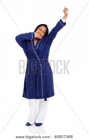 young sleepy indian woman yawning and stretching before bedtime isolated on white