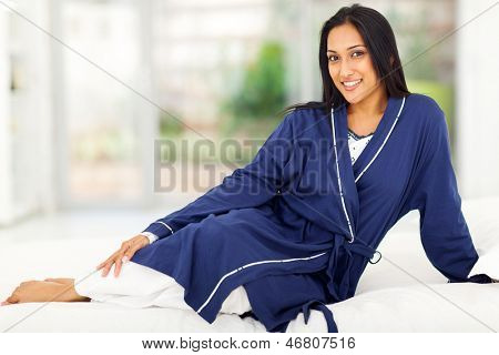 beautiful indian woman in nightclothes relaxing on bed