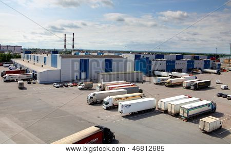 Cargo Terminal In A Large Warehouse Complex. Trucks Unload, Unloading Or Waiting In The Parking Lot