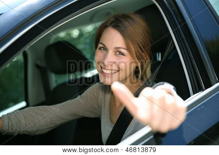Cheerful girl sitting inside car with thumb up