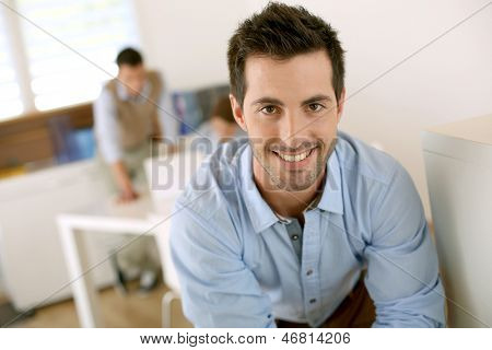 Smiling successful man standing in office