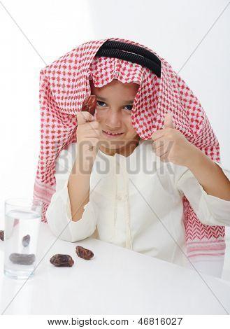 A little muslim boy wearing islamic attire ready for braking Ramadan fast