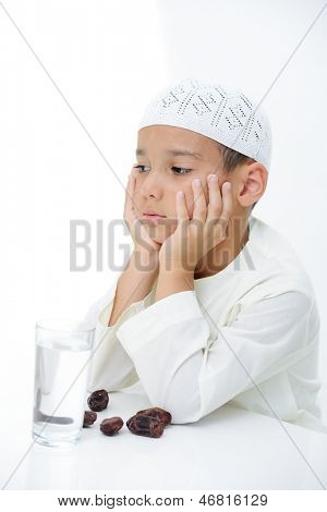 A little muslim boy wearing islamic attire ready for braking Ramadan fast