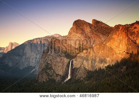 Yosemite at sunset as seen from the Tunnel View viewing point, showing the Half Dome, Cathedral Rocks and the Bridalveil Falls being lit by the setting sun. Yosemite National Park, California, USA