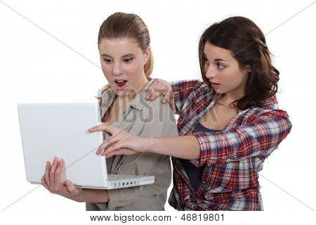 Two shocked girls looking at laptop