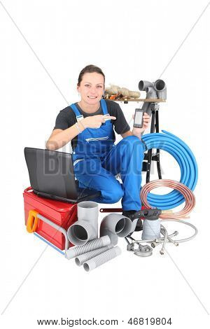 Female plumber with tools of the trade, laptop computer and smartphone