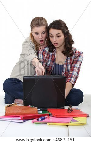 Two female student on a computer.