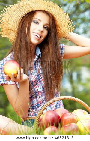 Apple woman. Very beautiful ethnic model eating red apple in the park.