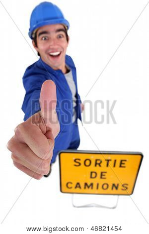 Cheerful construction worker with thumb up
