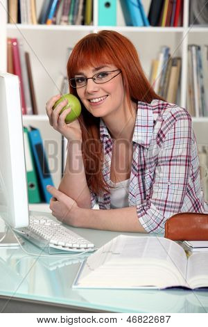 Young student holding apple in library