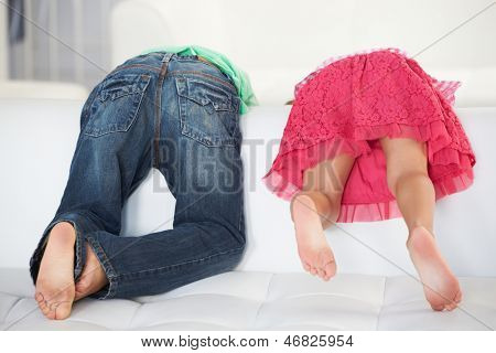 Rear View Of Two Children Playing On Sofa